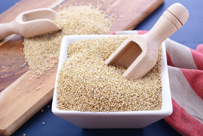 White grain quinoa with wooden scoops and chopping board on dark blue wood background, closeup.