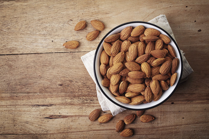 White bowl of almonds on wooden background