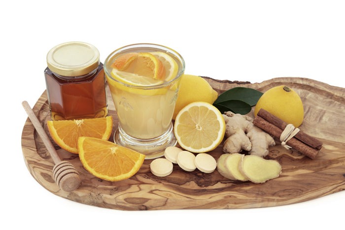 Cold and flu healing drink with vitamin c tablets, orange, lemon, ginger and cinnamon spice on olive wood board over white background.