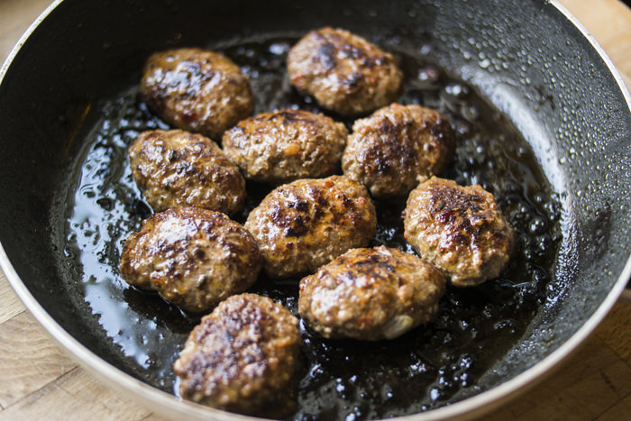 Meatballs are frying in a pan.