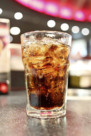 Glass of cola on a table in a restaurant,Soda beverage for quenching thirst.