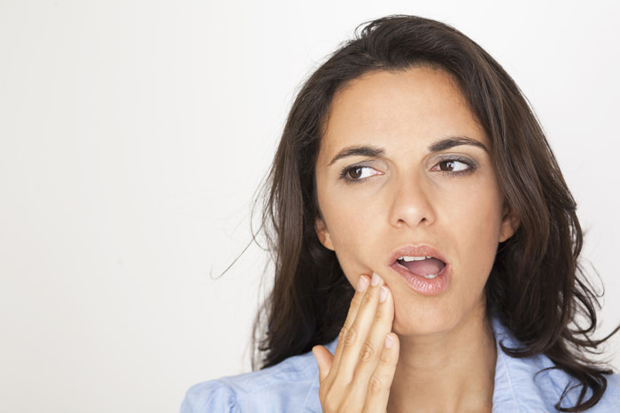 Young latin woman having toothache