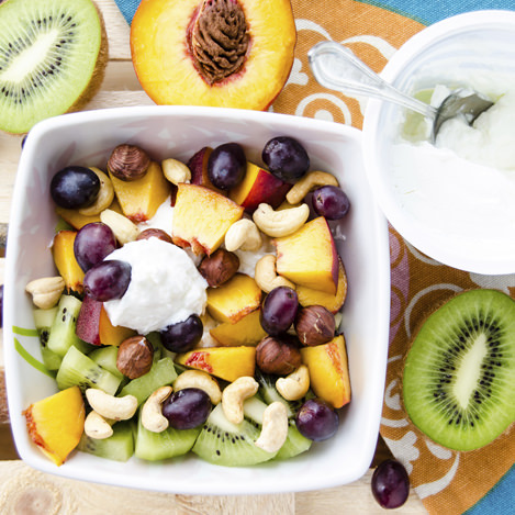 Cottage cheese with fruit and nuts and halves kiwi and peach. Concept of healthy eating for breakfast