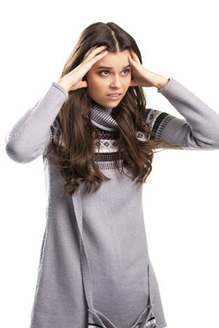 Lady in pullover touches face. Young woman with brown hair. Weak and vulnerable. Prepare for the worst.