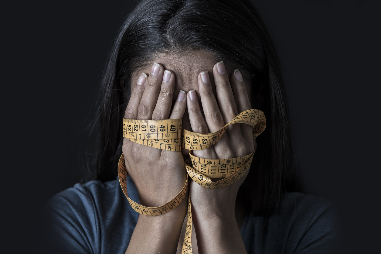 Verzweifelte Frau mit Maßband in der Hand