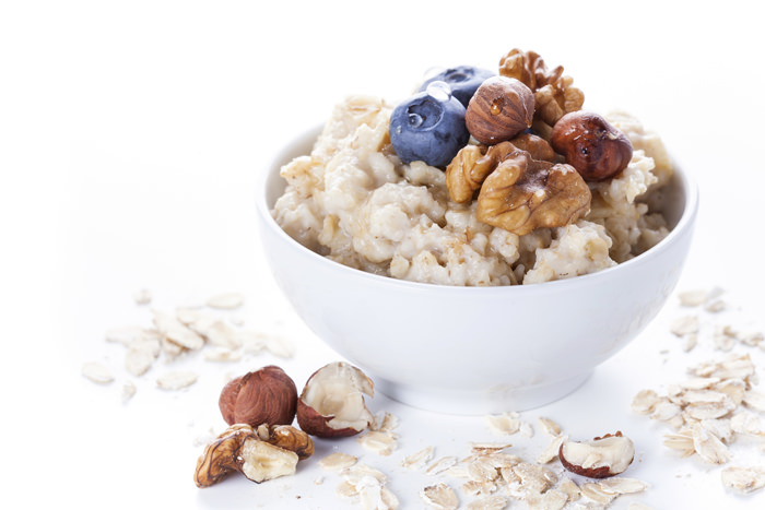 Oatmeal porridge in bowl topped with fresh blueberries, nuts and honey on white background