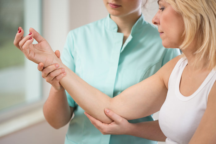 Close-up of young physiotherapist flexing the elbow