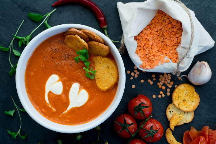 Soup made of baked cherry tomatoes and red lentil with fresh marjoram.