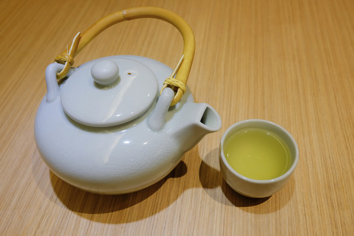 A cup of japanese green tea with teapot on wooden table