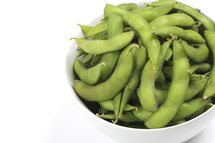 Whole edamame pods (green soybeans), cooked and ready to eat.