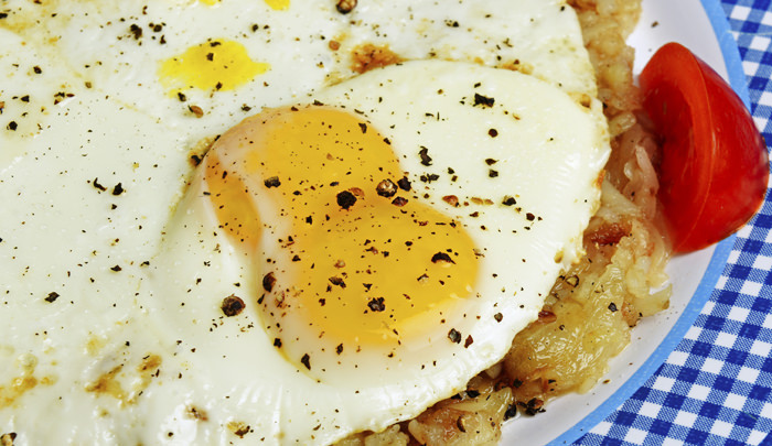 Fried eggs with intact yolks served over hash brown potatoes with tomato garnish on checkered blue plate