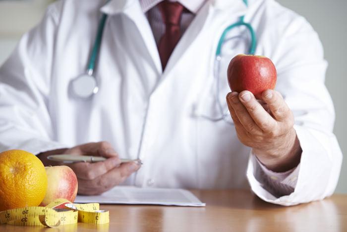 Arzt hält Apfel in der Hand