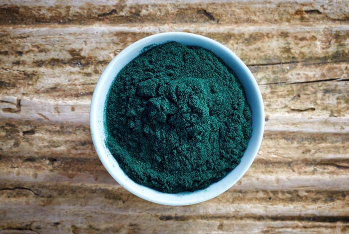 bowl of spirulina algae powder on wooden background, top view