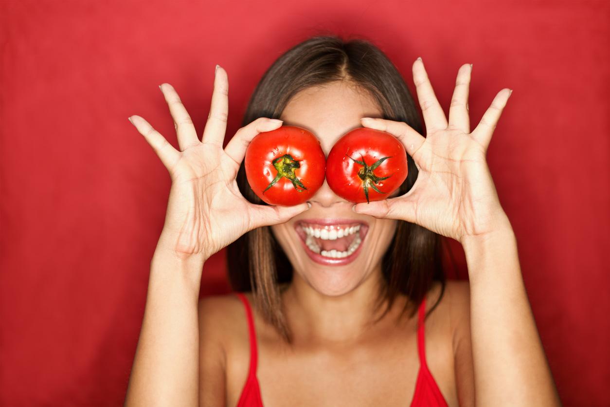glückliche Frau hält Tomaten vor Augen
