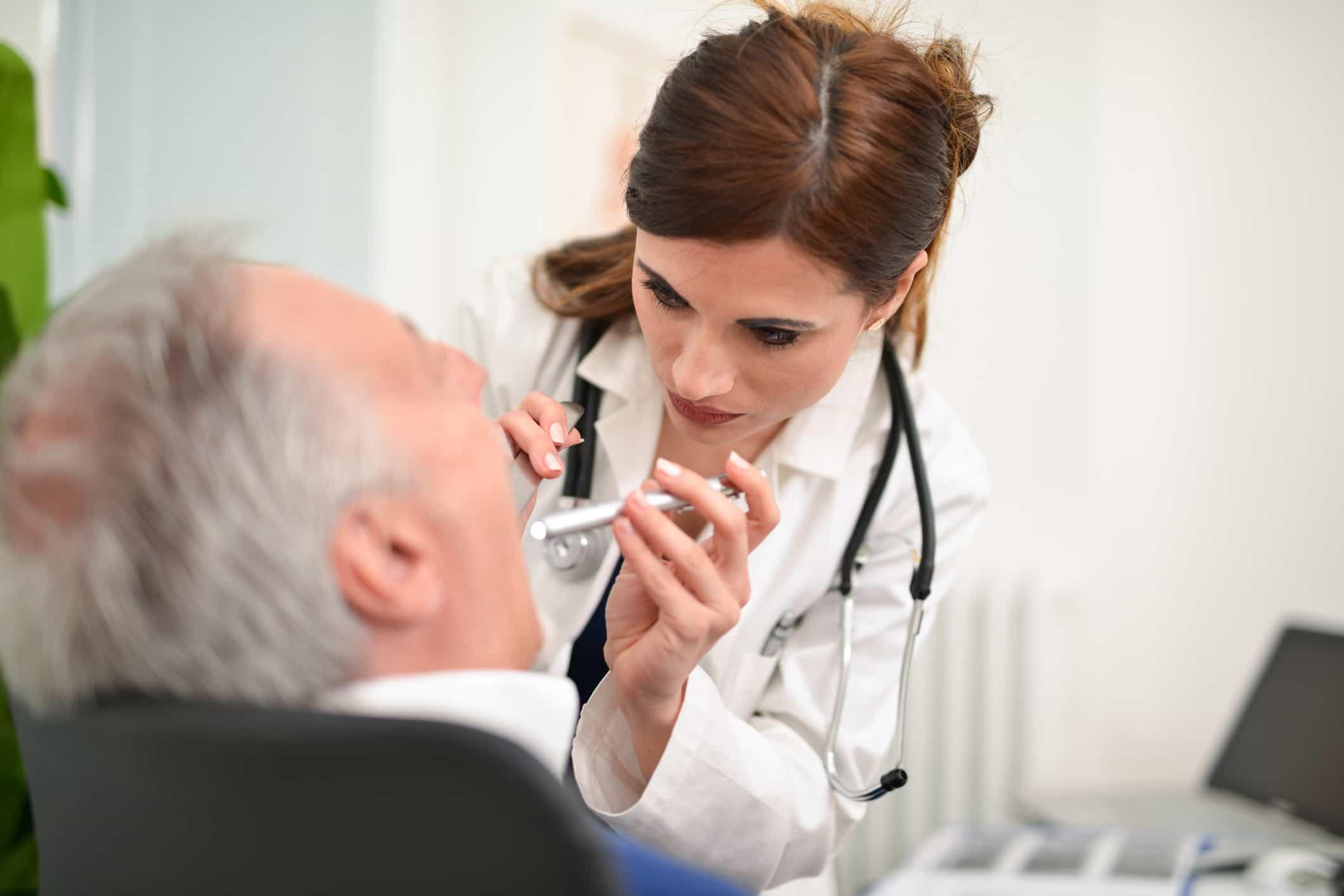 Ärztin untersucht Mund eines Patienten