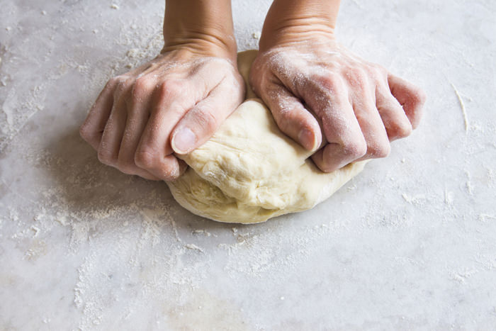 Hands knead dough on cutting board for homemade bakery