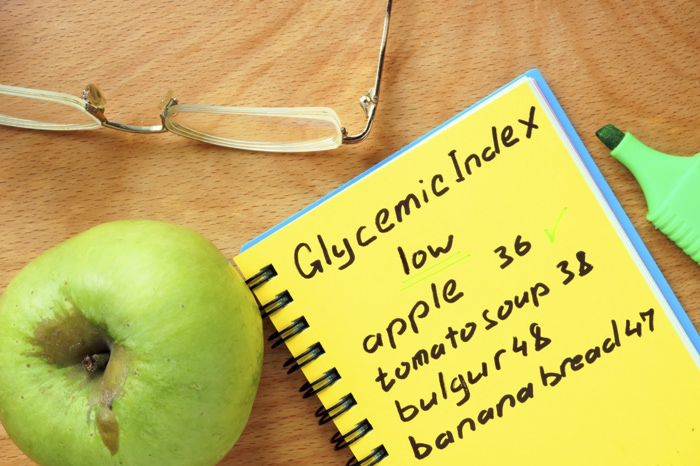 Foods with low Glycemic index list on a wood board.