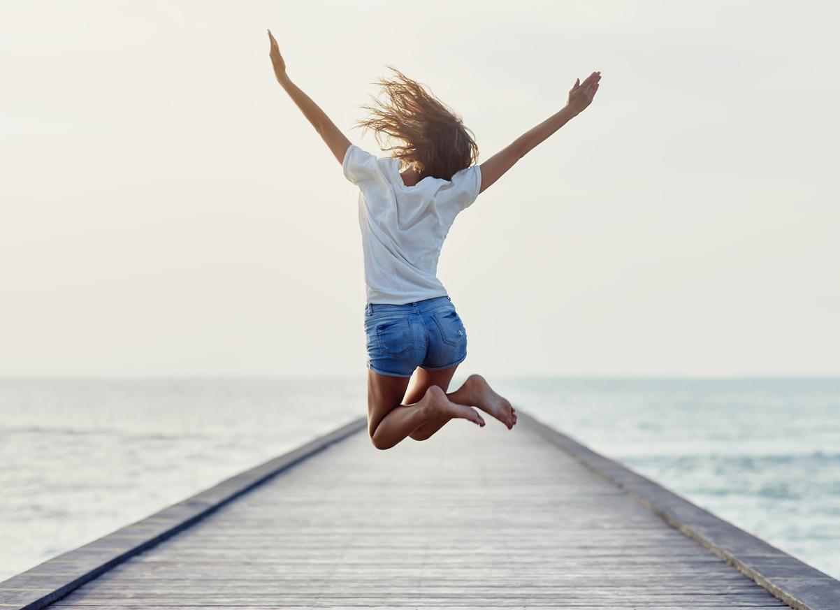 Frau ist glücklich am Meer auf einem Steg