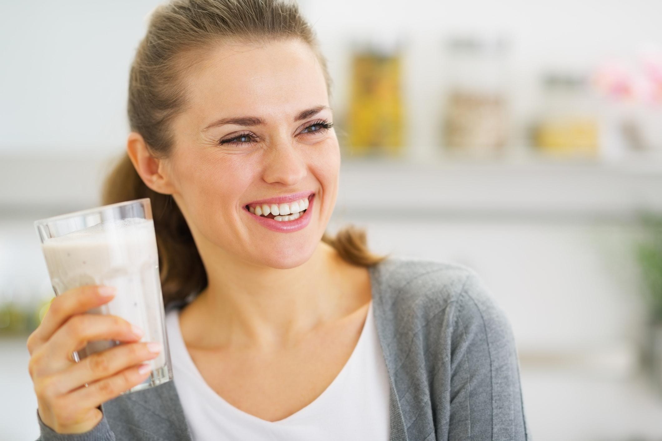 Glückliche Frau trinkt Milch
