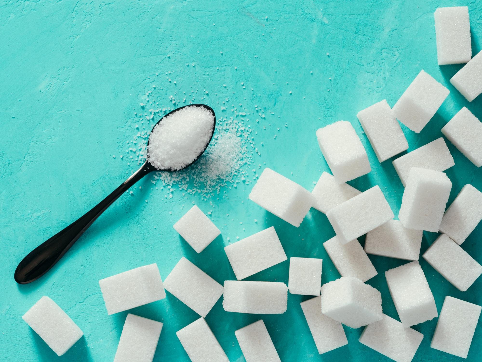 Zucker auf einem Löffel und in Würfeln